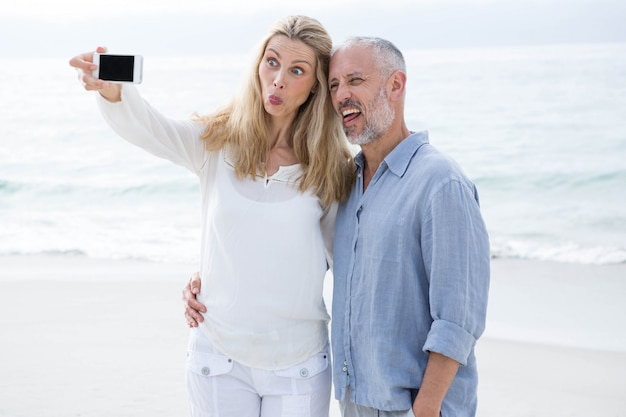 Happy couple taking selfie with mobile phone