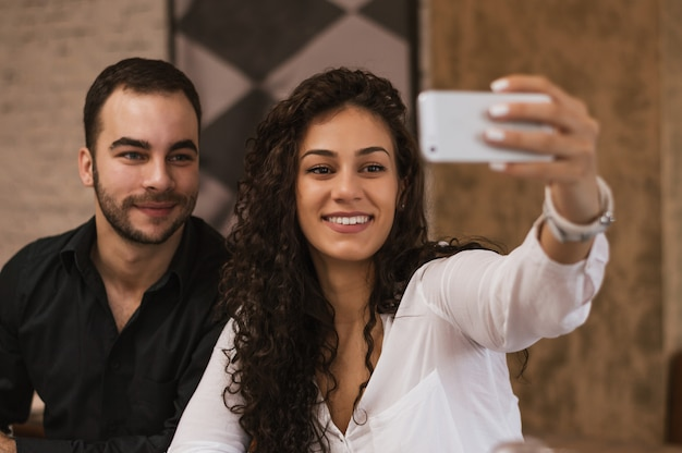 Happy couple taking selfie with smartphone at cafe.