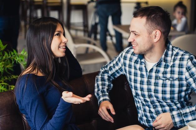 Счастливая пара разговаривает в кафе, пьет чай