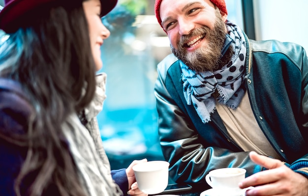 Happy couple talking and having fun together at bar cafeteria - selective focus on bearded guy