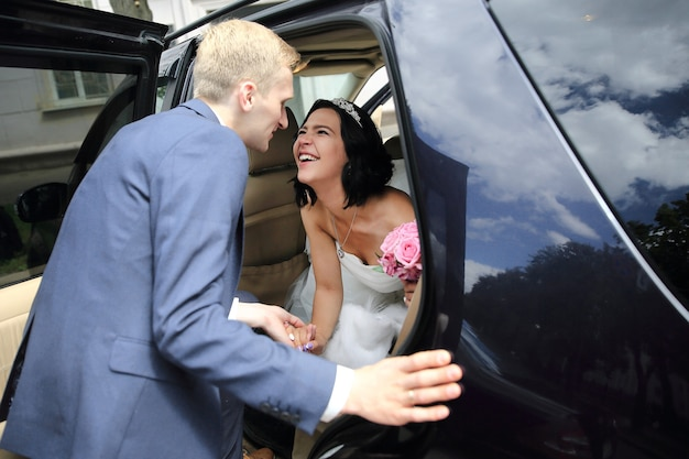 Happy couple talking near wedding limo.holidays and events