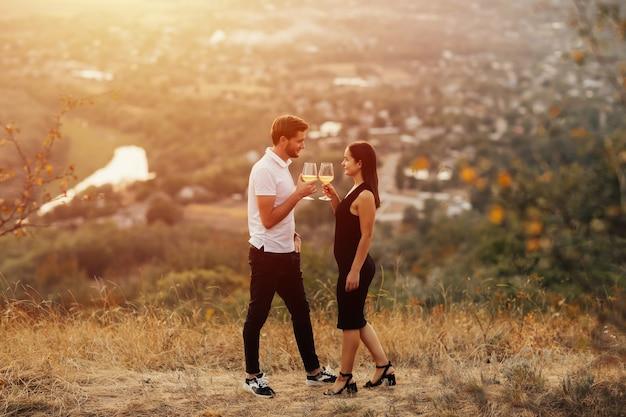 丘の上で白ワインのグラスを乾杯する幸せなカップル。一緒に立って白ワインを飲むロマンチックなデートのカップル。