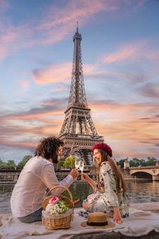 A happy couple toasts in front of the eiffel tower