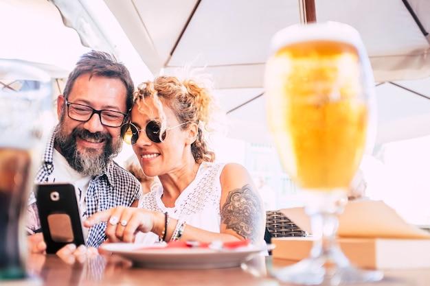 インターネットのモダンな接続アクティビティで電話デバイスを楽しんでいるレストランで一緒に幸せなカップル-ビールと幸せとバーで屋外レジャー活動で陽気な大人の人々