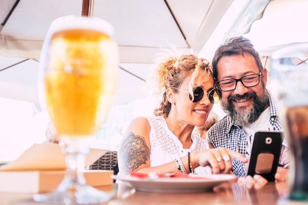 인터넷 현대 연결 활동으로 전화 장치를 즐기는 레스토랑에서 함께 행복한 커플