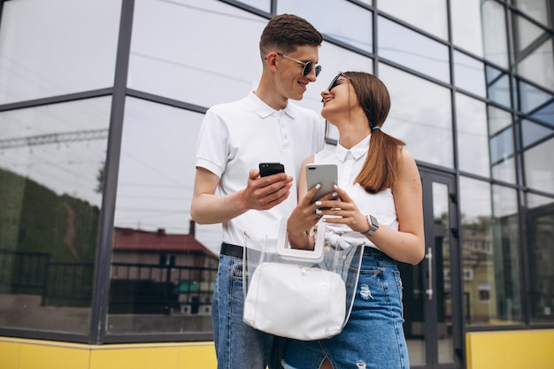 Happy couple together out in the city using phone
