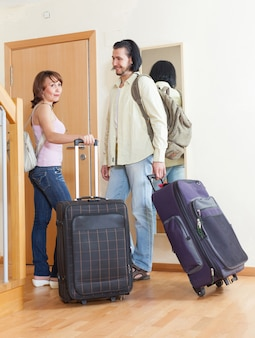 Happy couple together with luggage leaving