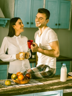 Happy couple toothy smiles at kitchen interior