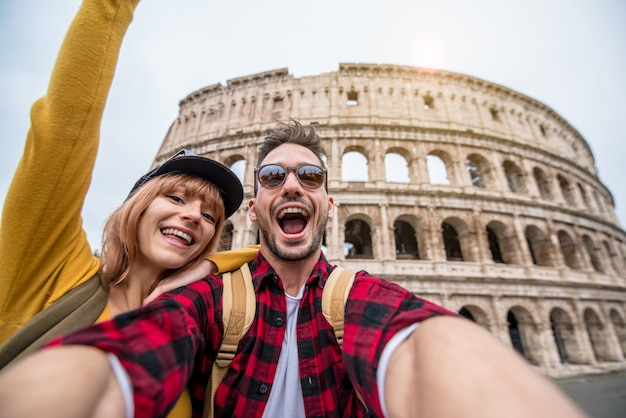 Happy couple of tourist having fun taking a selfie in front of colosseum in rome.