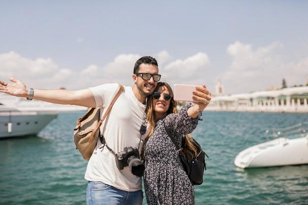 海の前で携帯電話で自分の肖像画を撮っている幸せなカップルの観光客
