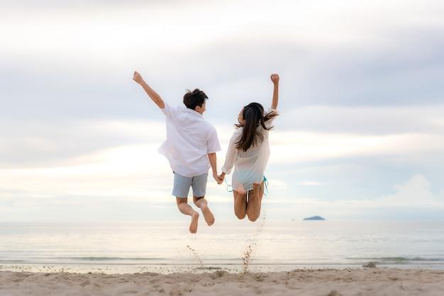 Счастливая пара туристов прыгает на пляжные каникулы. концепция путешествия молодой пары, приветствующей летние каникулы, показывая успех, счастье и радость на идеальном белом песчаном тропическом пляже под солнцем.