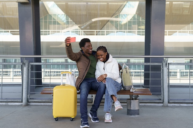 Happy couple of tourists take selfie at airport after arrival loving african man and woman laughing