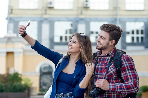 Happy couple of tourists taking selfie in showplace of city