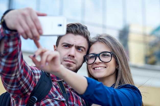 Happy couple of tourists taking selfie in showplace of city.