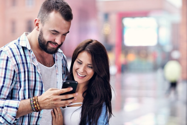 Happy couple of tourists using smartphone in city in rainy day