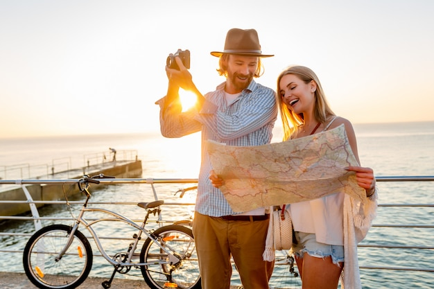 幸せなカップルの夏の自転車旅行、地図を見て、カメラで写真を撮る