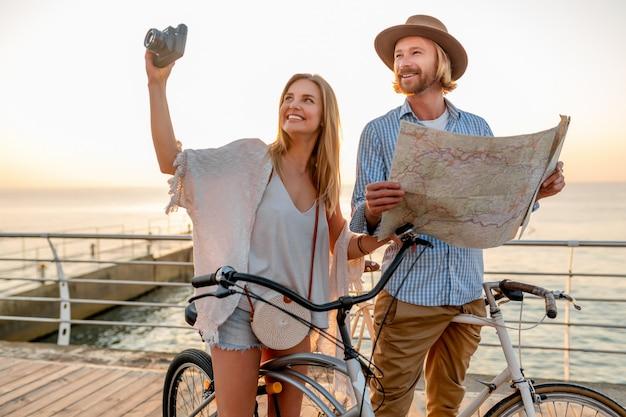 幸せなカップルの夏の自転車旅行、地図の観光を見て写真を撮る