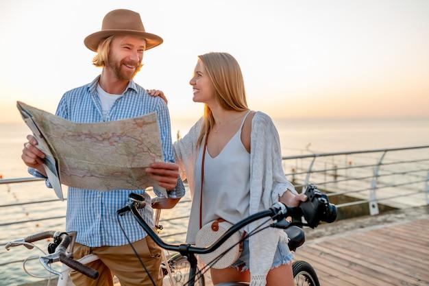 Счастливая пара путешествует летом на велосипедах, глядя на карту достопримечательностей