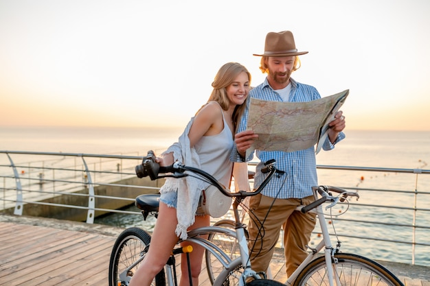 幸せなカップルが夏に自転車で旅行、地図観光で探して