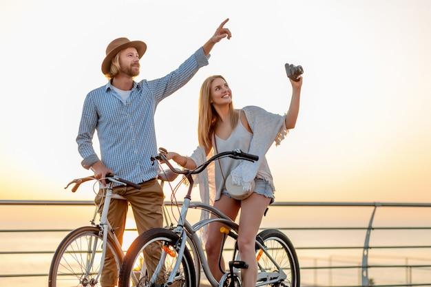 幸せなカップルの夏に自転車で旅行、写真を撮る
