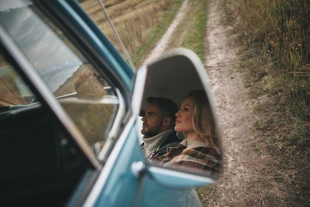 행복 한 커플 여행입니다. 복고풍 미니 밴에 앉아 멀리 바라보고 웃고 있는 아름다운 젊은 부부의 모습