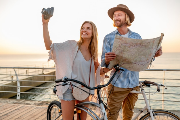 Happy couple traveling in summer on bicycles, looking in map sightseeing and taking photos