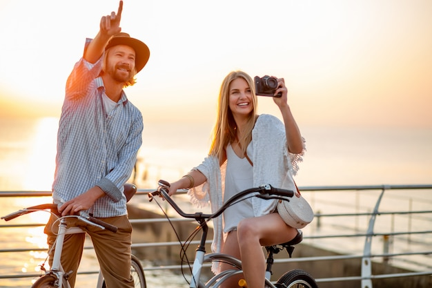Happy couple traveling in summer on bicycles, taking photos