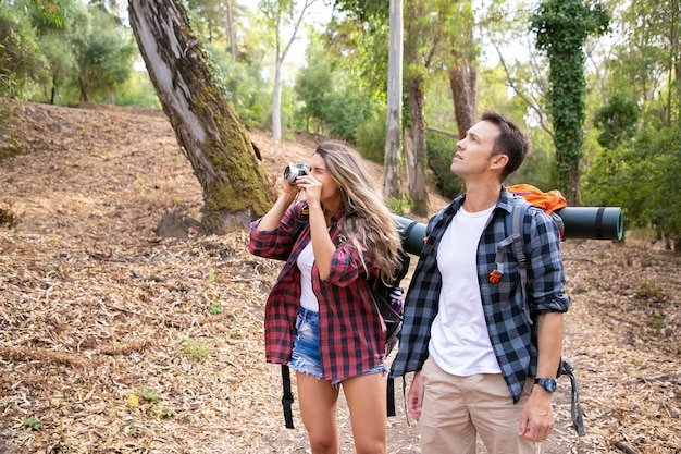 Happy couple traveling together, taking photos and hiking in forest. two caucasian backpackers walking through woods. woman shooting nature on camera. tourism, adventure and summer vacation concept