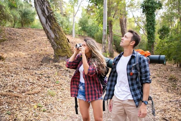 Coppia felice che viaggiano insieme, scattare foto e fare escursioni nella foresta. due viaggiatori con zaino e sacco a pelo caucasici che camminano attraverso i boschi. donna che riprende la natura sulla fotocamera. concetto di turismo, avventura e vacanze estive