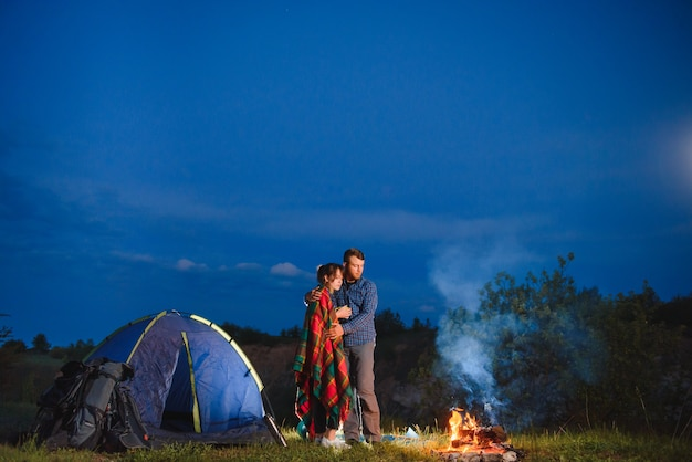 Счастливая пара путешественников, сидящих вместе у костра и светящейся туристической палатки