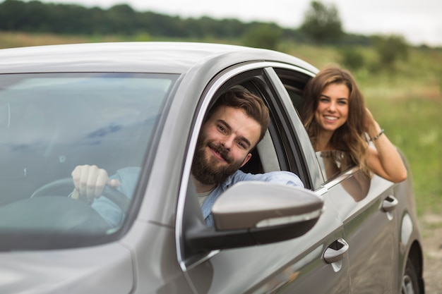 Happy couple travelling in car