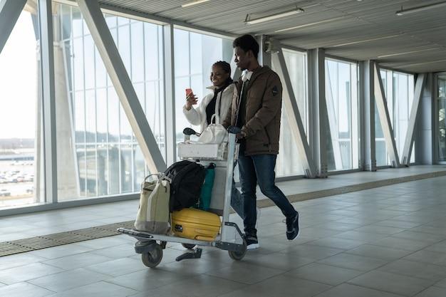 Счастливая пара путешествует после пандемии коронавируса в аэропорту с багажом