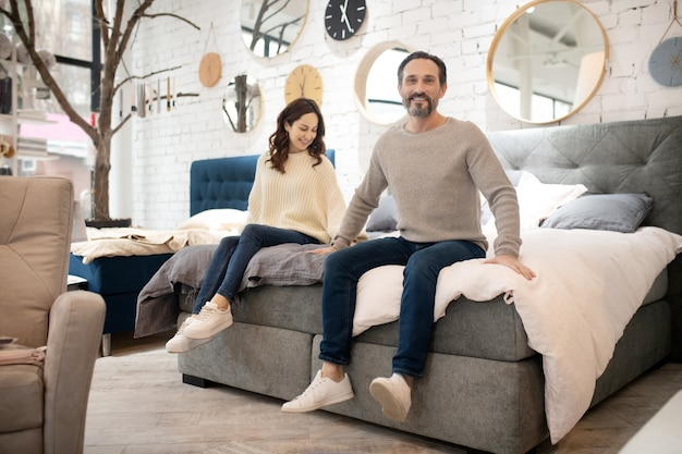 Happy couple trying new bed in furniture salon