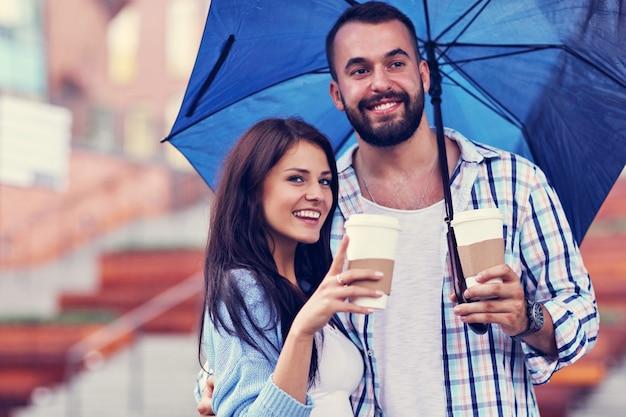 街の傘の下で幸せなカップル