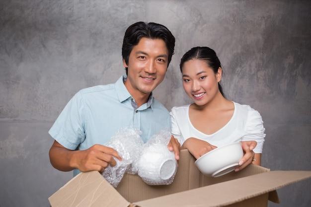 Happy couple unpacking moving boxes