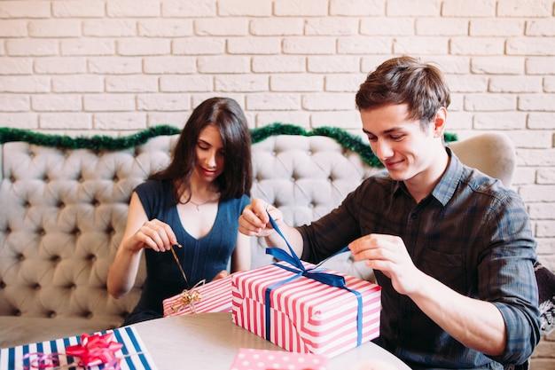 クリスマスプレゼントを開梱する幸せなカップル