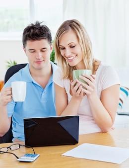 Счастливая пара, используя ноутбук, сидел вместе за столом, держа чашки кофе