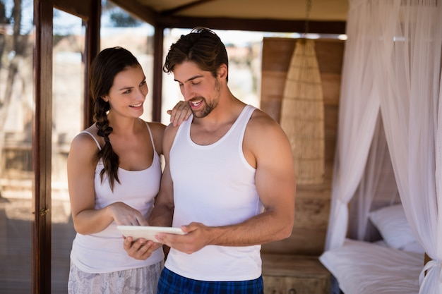 Happy couple using digital tablet in cottage