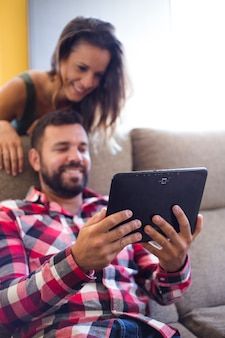 Happy couple using digital tablet at home