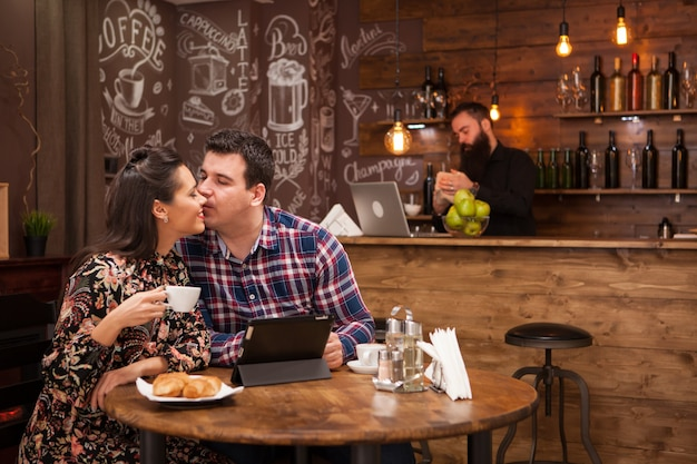 Happy couple using digital tablet while having coffee at restaurant. hipster restaurant.