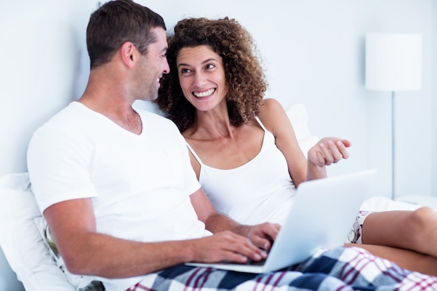 Happy couple using laptop on bed