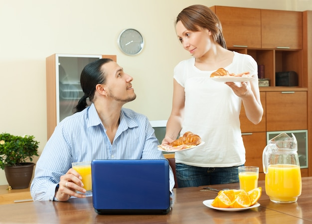 Happy  couple using laptop during breakfast