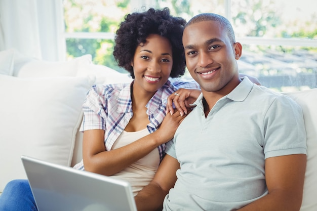 Happy couple using laptop on the sofa at home