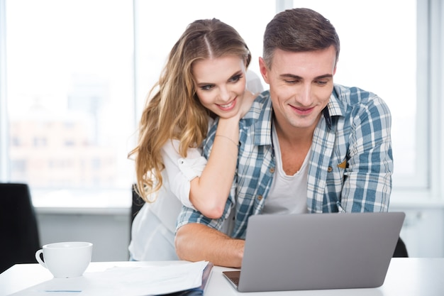 Happy couple using laptop and surfing in internet sitting at the table