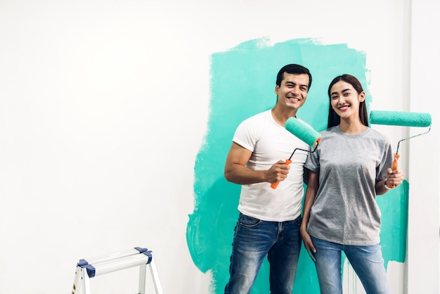 Happy couple using paint roller and painting wall