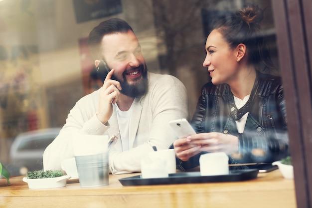 レストランで電話を使用して幸せなカップル
