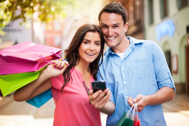 Happy couple using smart phone during the shopping