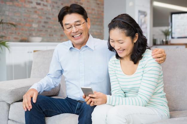 Happy couple using smartphone on the sofa