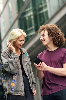 Happy couple using smartphone in urban background.