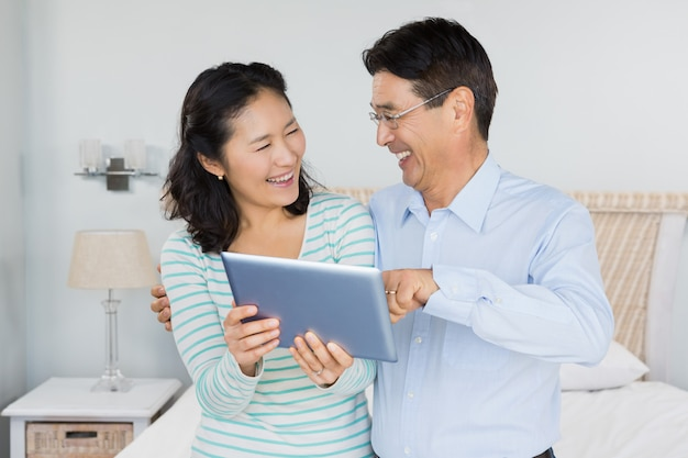 Happy couple using tablet in bedroom